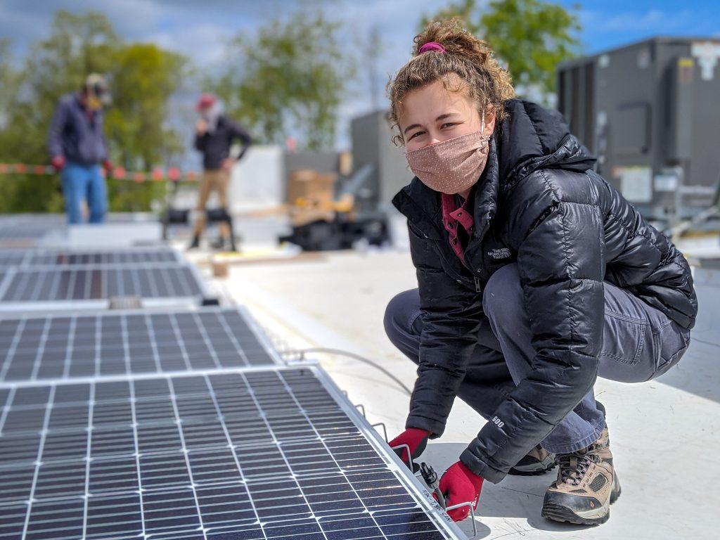 woman wearing mask installing solar